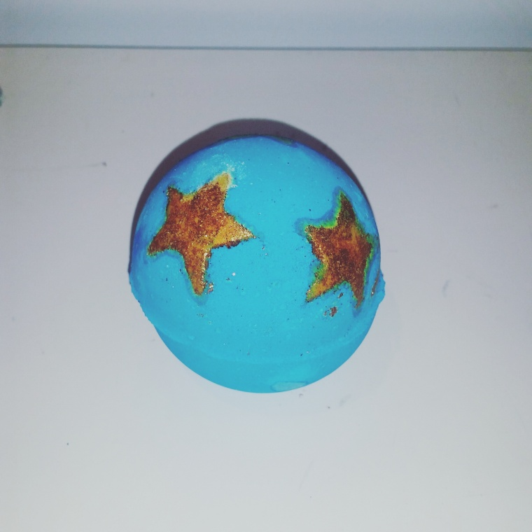 Three gold sparkly stars are placed in the top half of the round blue sphere.