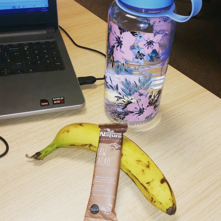 A creative nature superfoods raw cacao bar leans with a banana and a bottle of water