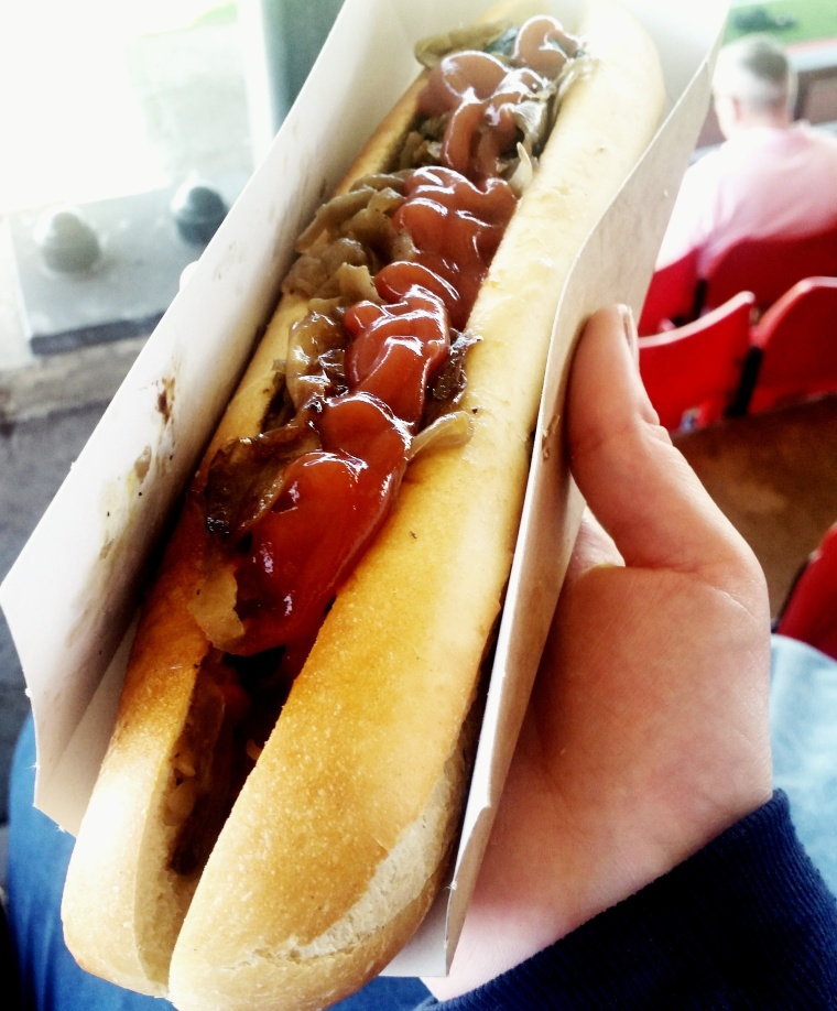 A long baguette with two sausages, onion, mushroom and ketchup on top