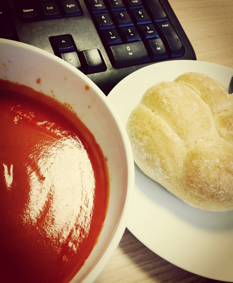 Bowl of tomato soup with a fresh warm bread roll at an office desk with the keyboard in the background