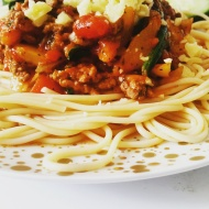 Beef mince bolognese rests on spaghetti with a sprinkling of cheese and a side salad