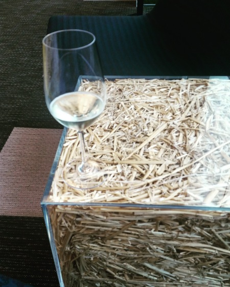 Wine glass of prosecco on a plastic box of hay