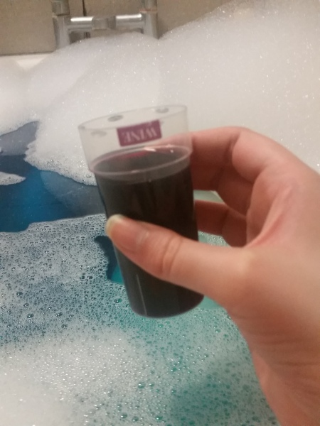 Mini little plastic cup filled with red wine