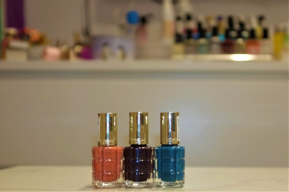 Three nail varnishs, pink, purple and blue by L'Oreal