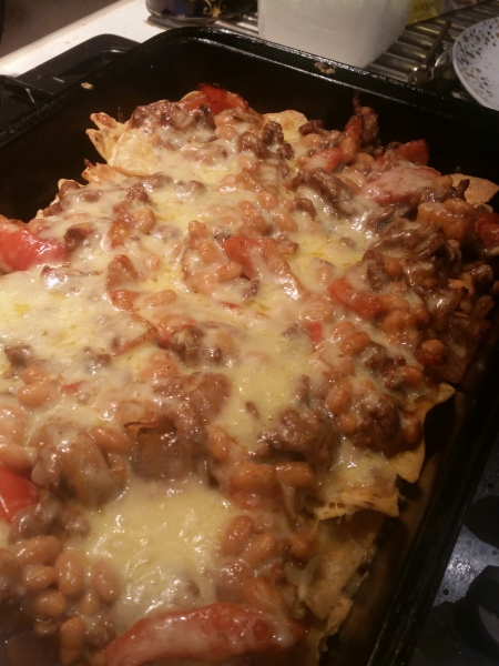 nachos, cheese and other loaded ingredients in a tray