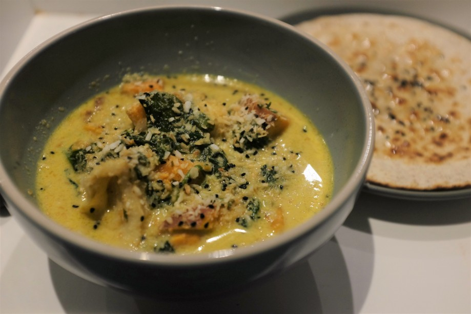 Light yellow creamy curry with fish, butternut squash and herbs sticking out of the top