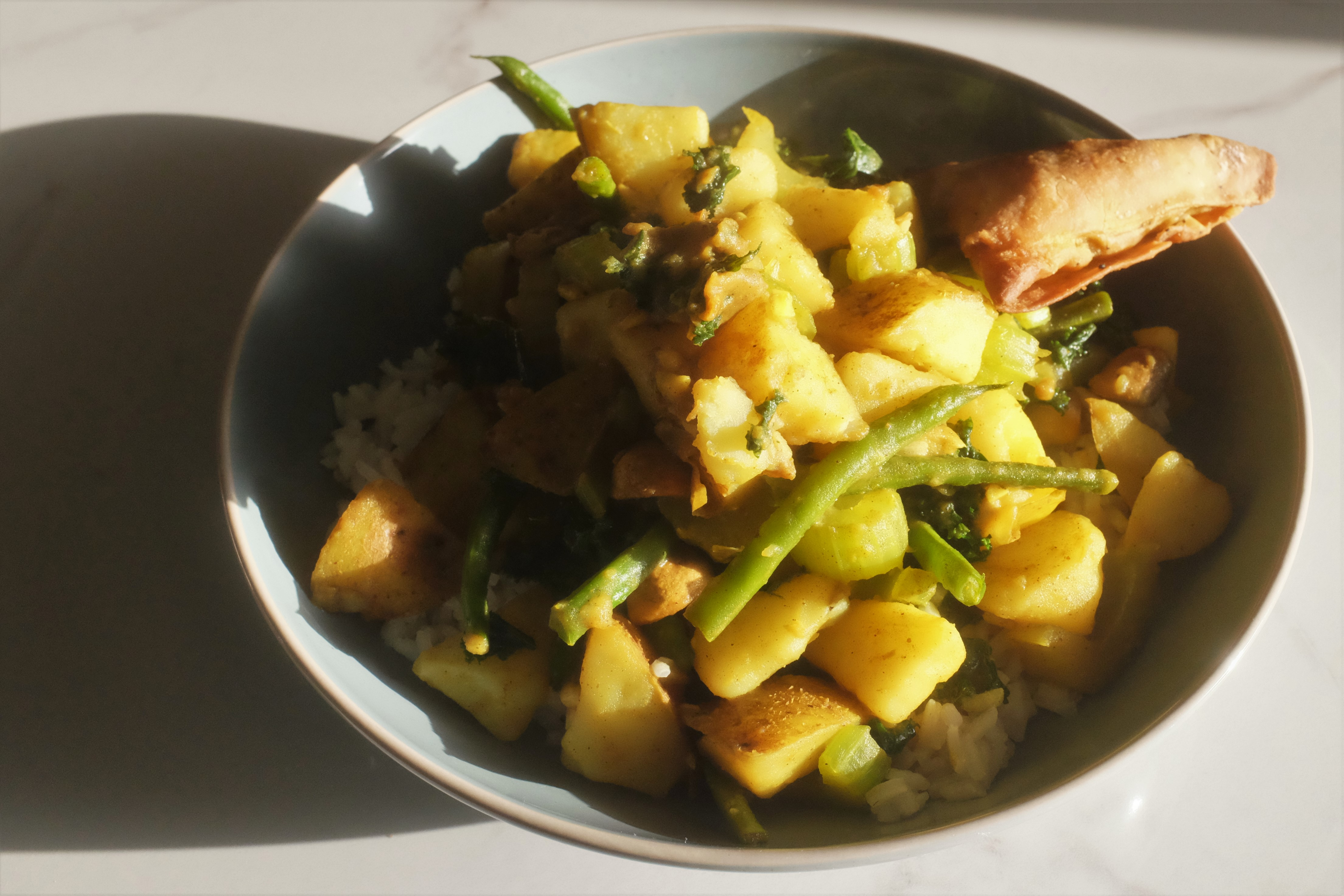 Vegetable and potato curry on a bed of rice in a large bowl